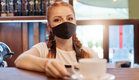 Barista mit Mundschutz stellte eine Tasse Kaffee auf den Tresen © sementsova321, stock.adobe.com