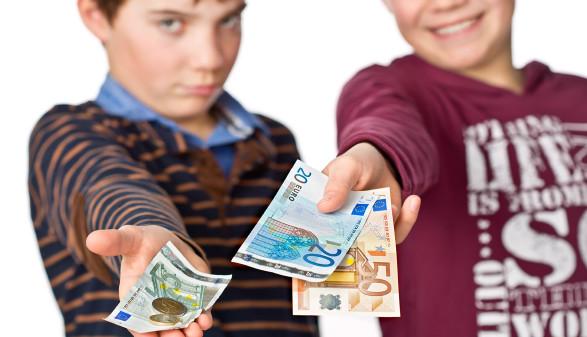Zwei Kinder halten Bargeld in der ausgestreckten Hand. Eines der beiden hat deutlich mehr als das andere. © Markus Bormann, stock.adobe.com