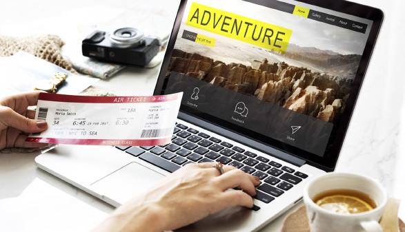 Man sieht die Hände einer Frau, in der linken hält sie ein Flugticket, mit der rechten tippt sie auf einer Notebooktastatur. © Rawpixel.com, stock.adobe.com