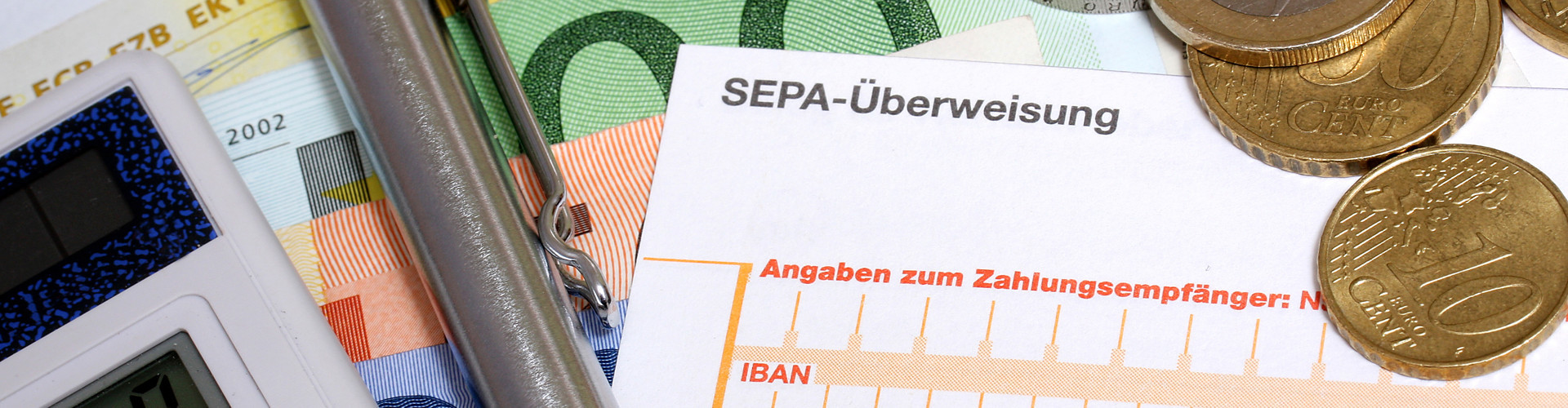 """Auf mehreren Geldscheinen liegen Taschenrechner, Kugelschreiber, einige Euromünzen und ein Erlagschein. Zu erkennen ist die Aufschrift """"SEPA-Überweisung"""". © RRF, stock.adobe.com"""