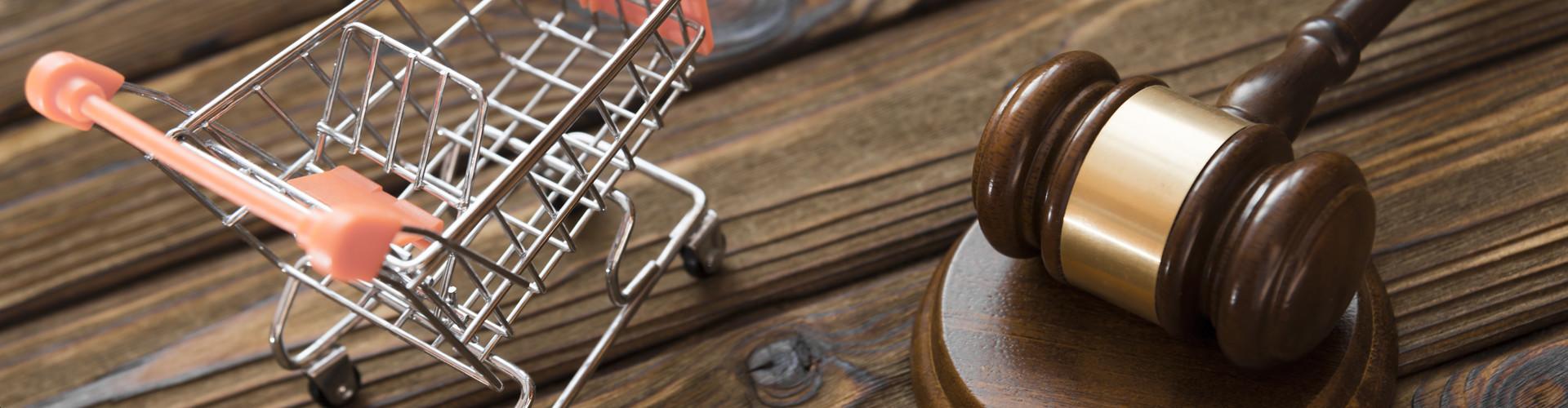 Neben einem Richterhammer steht die Miniatur eines Einkaufswagens auf einem hölzernen Untergrund © gerasimov174, stock.adobe.com