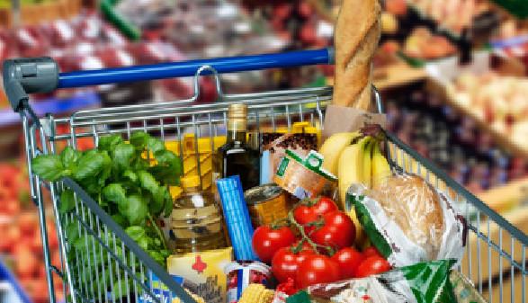Ein voller Einkaufswagen im Supermarkt, im Hintergrund sieht man unscharf das Gemüseregal © Eisenhans, stock.adobe.com