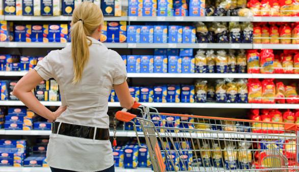 Frau steht mit Einkaufswagen vor Supermarktregal mit Markenprodukten © Gina Sanders, stock.adobe.com
