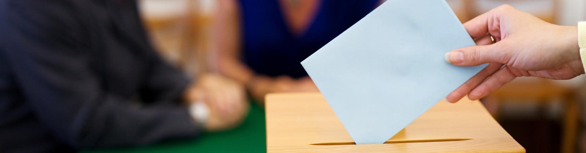 Vor unscharfem Hintergrund sieht man die Hand einer Frau, die ein Kurvert in eine Wahlurne steckt. © Gina Sanders, stock.adobe.com