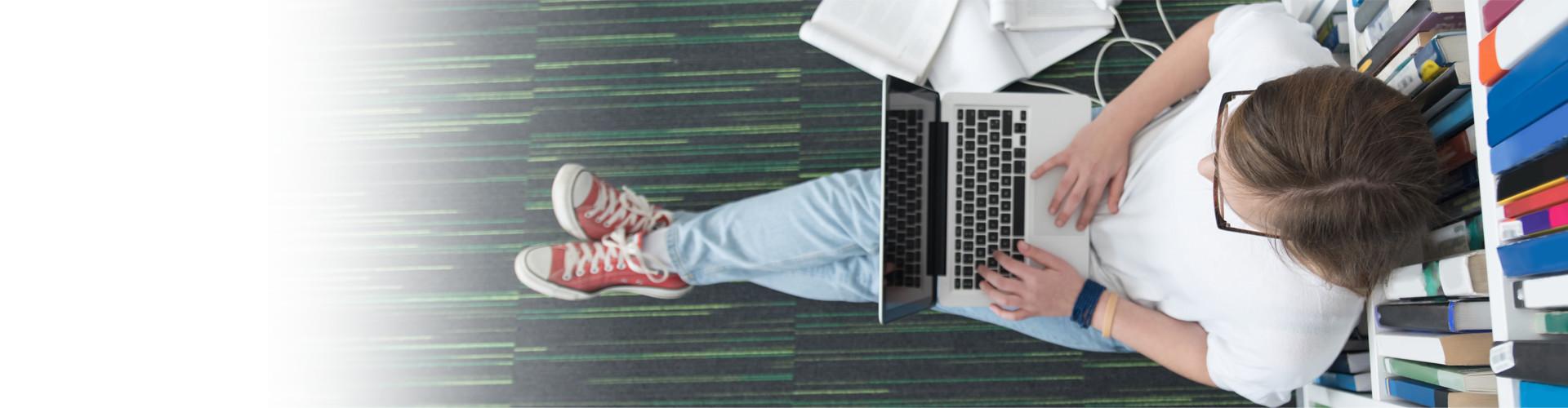 Von oben sieht man eine Studentin mit Notebook auf dem Schoß, welche auf dem Boden sitzt und an einem Bücherregal lehnt. © .shock, stock.adobe.com