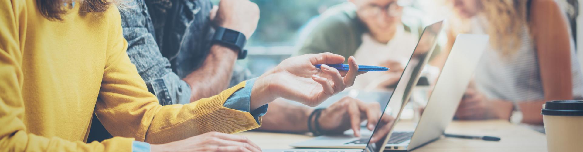 Mehrere Menschen sitzen gemeinsam mit Laptop an einem Tisch © Adobe Stock, Adobe Stock