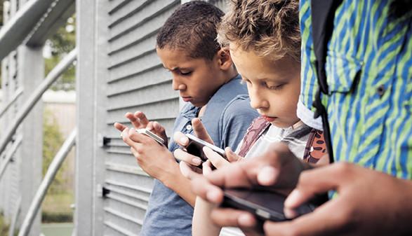 Kinder stehen nebeneinander und schauen in ihr Smartphone © bramgino, Fotolia